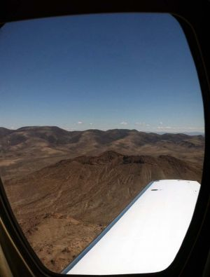 Travel_airplane_window_mountains_crater.jpg